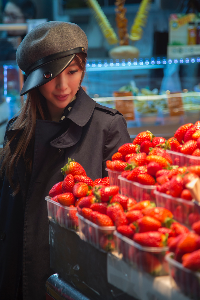 La Boqueria Market girl looking at strawberry