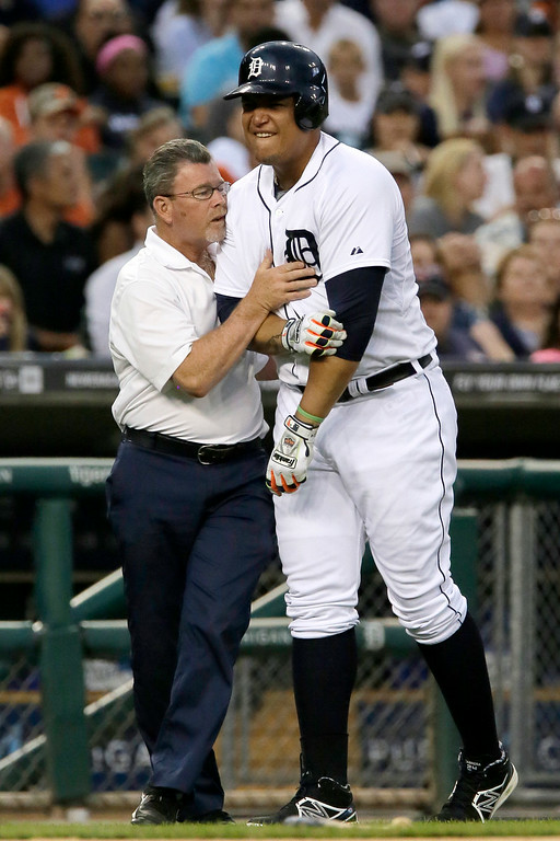 . Detroit Tigers\' Miguel Cabrera, right, grabs his elbow as trainer Kevin Rand tries to assist him after being hit with a pitch during the third inning of a baseball game against the Seattle Mariners, Saturday, Aug. 16, 2014, in Detroit. (AP Photo/Duane Burleson)