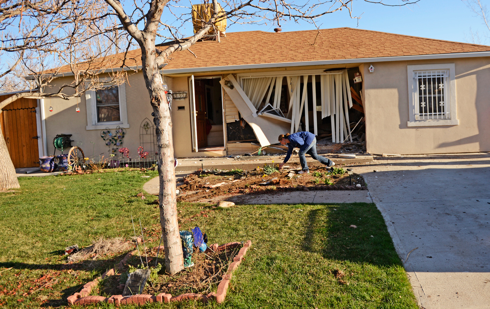 . Jessica Dominguez tries to fix the flowers outside her grandmothers home after an SUV crashed into the home, at the 5100 block of Gill Place in Denver, April 04, 2013. No one inside the home was hurt. (Photo By RJ Sangosti/The Denver Post)