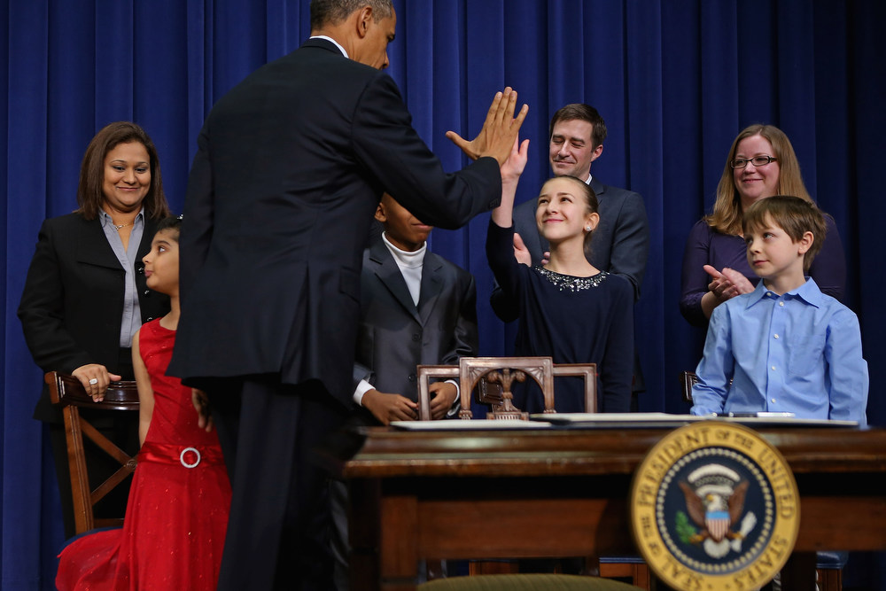 . U.S. President Barack Obama gives high-fives to children who wrote letters to the White House about gun violence, (L-R) Hinna Zeejah, Taejah Goode, Julia Stokes and Grant Fritz, after announcing the administration\'s new gun law proposals in the Eisenhower Executive Office building January 16, 2013 in Washington, DC. One month after a massacre that left 20 school children and 6 adults dead in Newtown, Connecticut, the president unveiled a package of gun control proposals that include universal background checks and bans on assault weapons and high-capacity magazines.   (Photo by Chip Somodevilla/Getty Images)