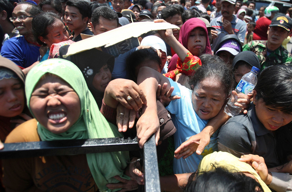 . Muslim women struggle to receive small packages of meat during the Eid al-Adha holiday in Gresik, East Java, Indonesia, Tuesday, Oct. 15, 2013. (AP Photo/Trisnadi)