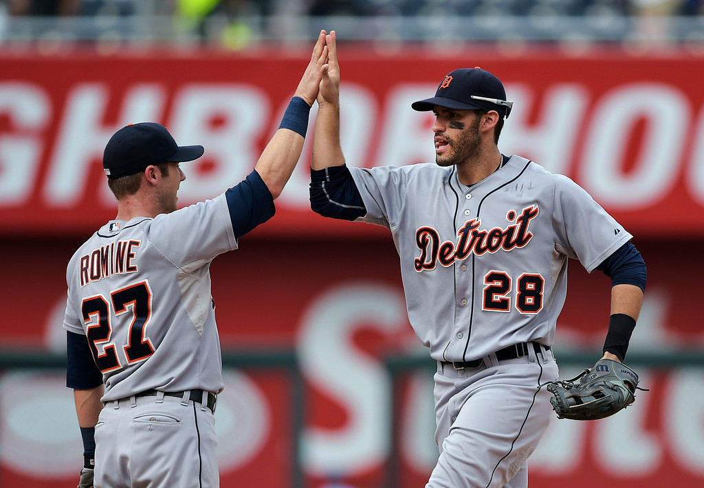 . Detroit Tigers shortstop Andrew Romine (27) high-fives J.D. Martinez (28) after defeating the Kansas City Royals in a baseball game Saturday, Sept. 20, 2014, in Kansas City, Mo. (AP Photo/Reed Hoffmann)