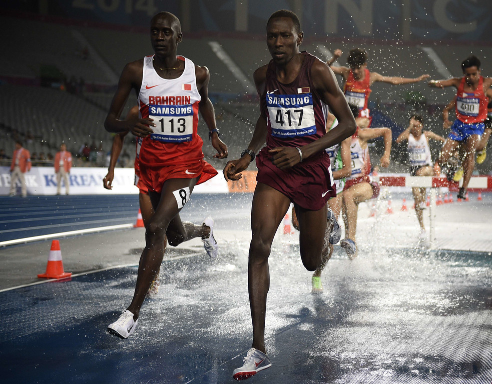 . Qatar\'s Abubaker Ali Kamal (R) runs after the water jump next to Bahrain\'s Tareq Mubarak Salem Taher (L) in the final of the men\'s 3000m steeplechase athletics event during the 17th Asian Games at the Incheon Asiad Main Stadium in Incheon on September 29, 2014. MARTIN BUREAU/AFP/Getty Images