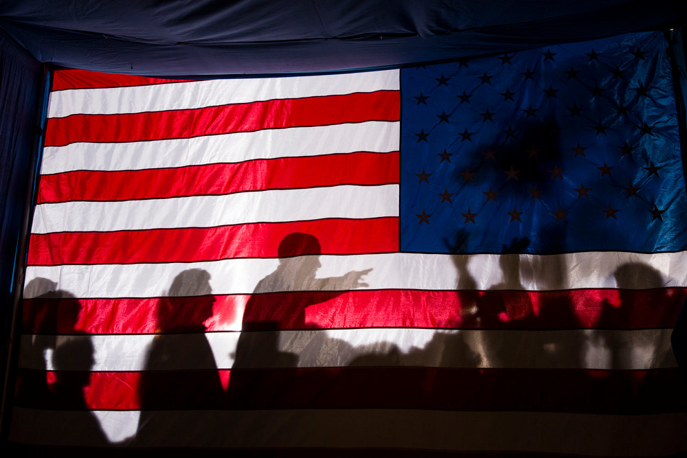 ". Nov. 3, 2012 ""I had noticed the possibility of a potential good photograph if the President were to pass by this flag as he departed an evening campaign rally in Dubuque, Iowa. So I planted myself backstage as he finished working a ropeline and managed to get one usable frame as he walked by.\"" (Official White House Photo by Pete Souza)"