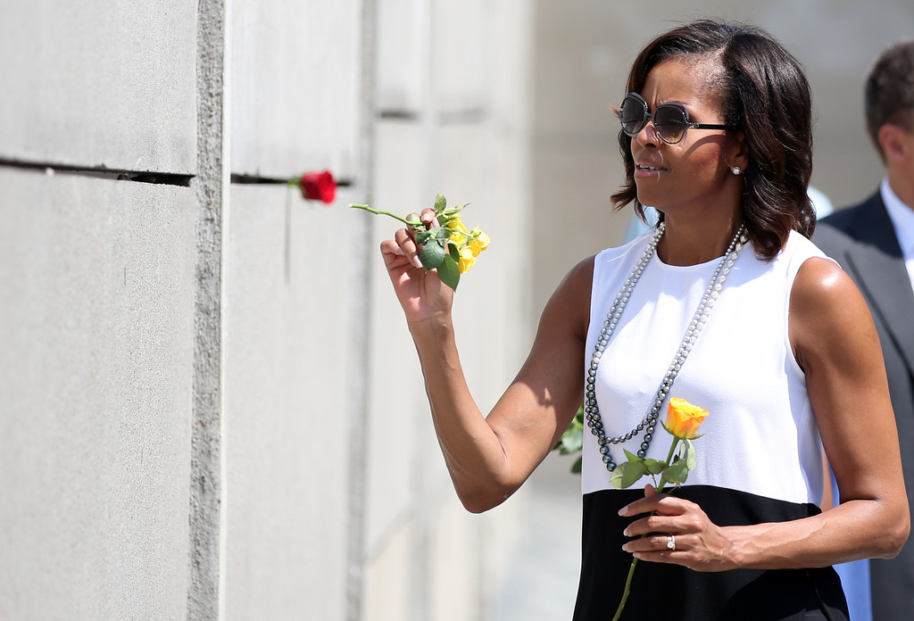 . US First Lady Michelle Obama lays flowers at the Berlin Wall memorial in Bernauer street on June 19, 2013 in Berlin. Obama\'s pay a two-day visit to Germany. Barack Obama arrived for his first visit as US president to Berlin Tuesday for talks with German Chancellor Angela Merkel and a major speech at the city\'s Brandenburg Gate. (Photo credit RONNY HARTMANN/AFP/Getty Images)