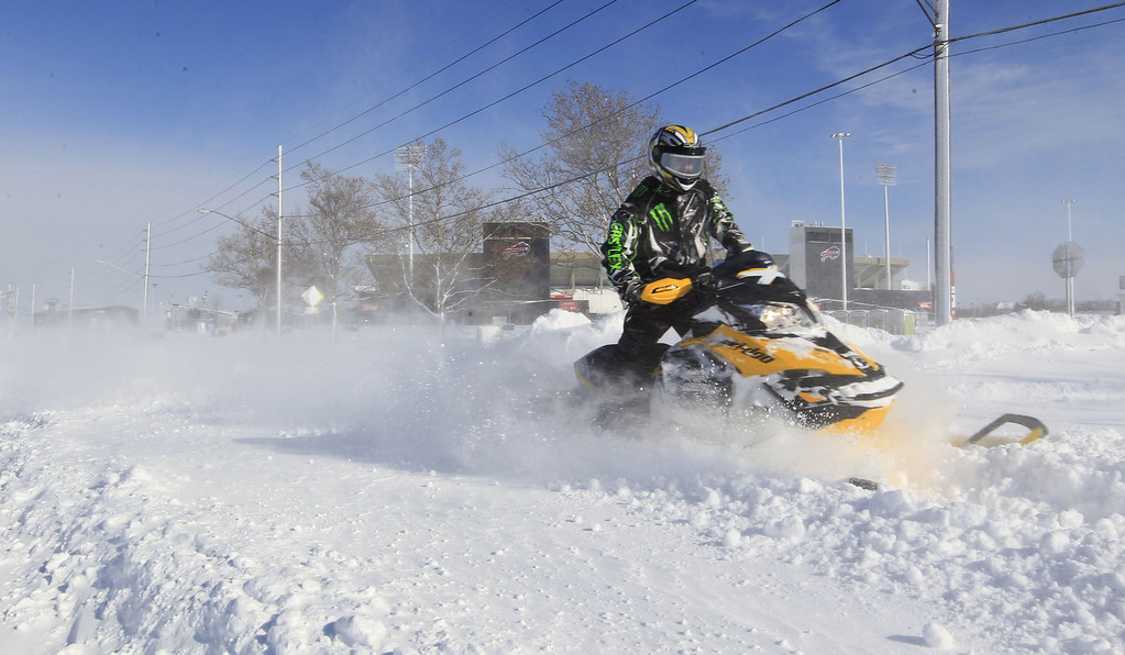 . A snowmobiler makes his way down Abbott Road in front of Ralph Wilson Stadium,  home of the Buffalo Bills,  in Orchard Park, N.Y. on  Wednesday, Nov. 19, 2014.  A ferocious lake-effect storm left the Buffalo area buried under 6 feet of snow Wednesday, trapping people on highways and in homes, and another storm expected to drop 2 to 3 feet more was on its way. (AP Photo/The Buffalo News, Harry Scull Jr.)