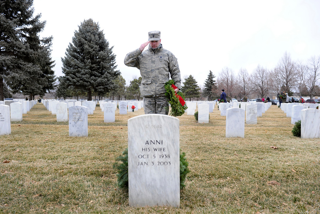 . Lt. Col. Bill Fellows from Schriever Air Force Base places a wreath along with other service members from the base located in Colorado Springs. Ft. Logan National Cemetery hosts its annual Wreaths Across America, a holiday wreath-laying ceremony on Sat. Dec. 15, 2012, that honors and remembers the nations\' veterans. After the ceremony, volunteers and families of loved-ones who are buried here, placed 1,000 wreaths in areas throughout the cemetery. Kathryn Scott Osler, The Denver Post