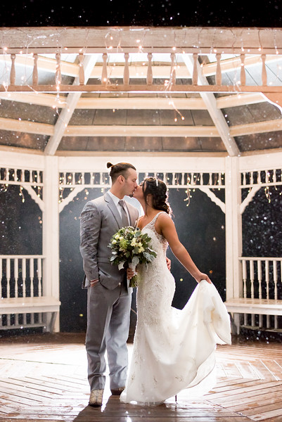 Bride and Groom kissing in the rain.