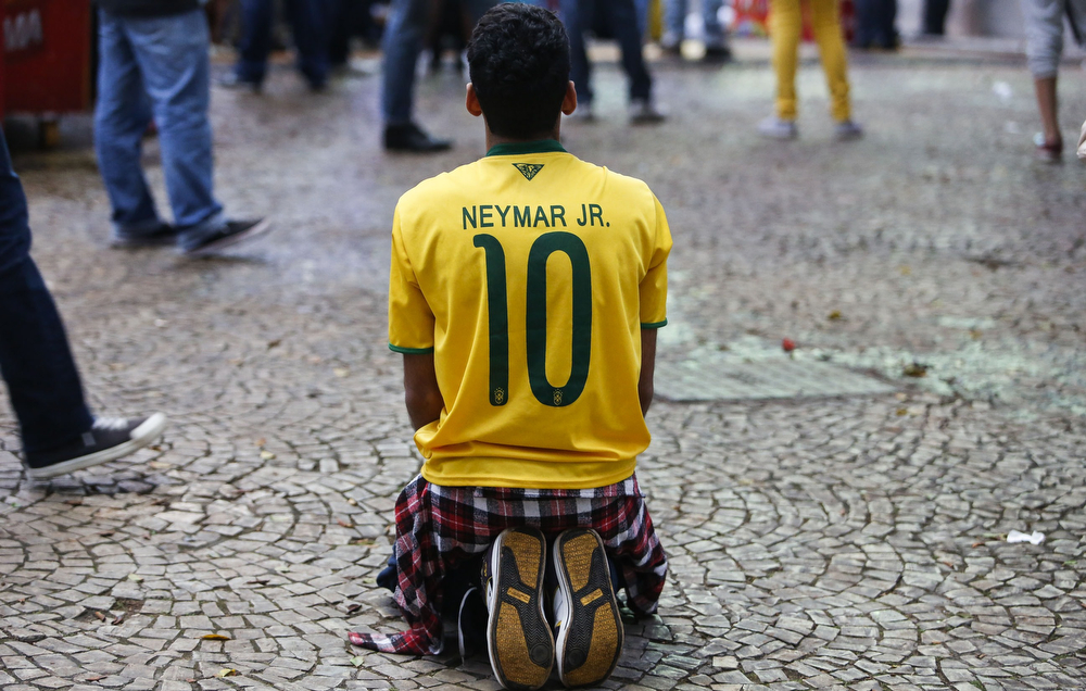 Description of . A fan of Brazil kneels in dejection as he watches the FIFA World Cup semi-final football match between Brazil and Germany at the Fan Fest public viewing event in Sao Paulo, Brazil, on July 8, 2014. (Miguel Schincariol/AFP/Getty Images)