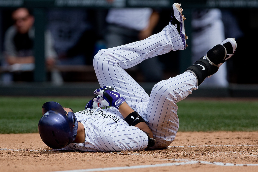 . Carlos Gonzalez #5 of the Colorado Rockies lies on the ground after getting hit by a pitch during the third inning against the San Diego Padres at Coors Field on May 18, 2014 in Denver, Colorado. The Rockies defeated the Padres 8-6 in 10 innings. (Photo by Justin Edmonds/Getty Images)