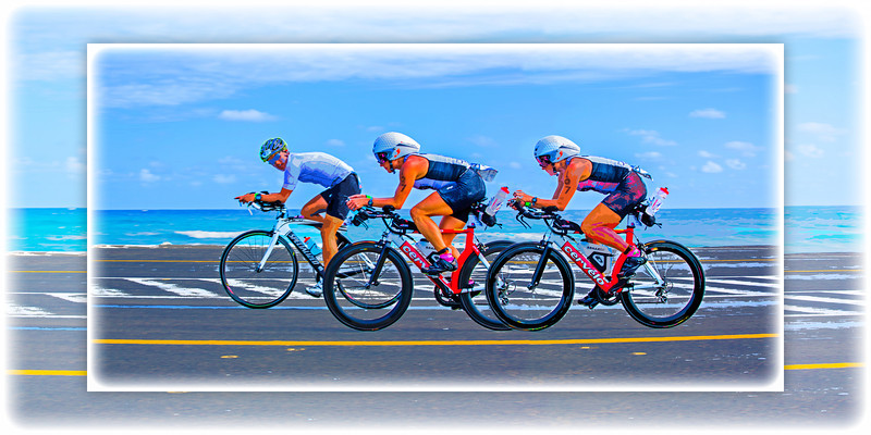 "The Overtake… Racing during the 112-mile cycling stage of Ironman Cozumel 2013 along the Playa Oriente area of Punta Morena near Mezcalitos on the east side of the island. This image is exactly the same as the adjacent one, but an artistic frame has been added. The image is also composed to ideally yield a 16"" x 32"" print or canvas or any other 1:2 ratio size such as 12"" x 24""."