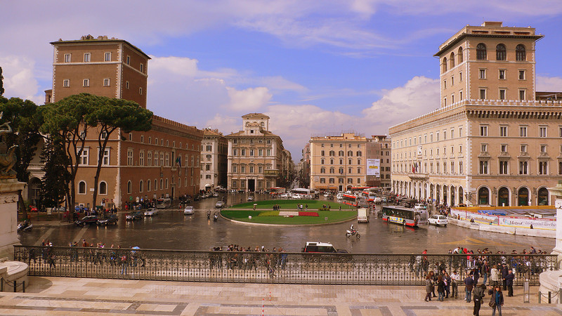 The Piazza Venezia seen from the Altare della Patria. On the left is the Palazzo Venezia, dedicated to St. Mark, a Papal palace completed in the mid-15th century. Mirroring the Palazzo Venezia in a lighter shade are the offices of an insurance company (Assicurazioni Generali).