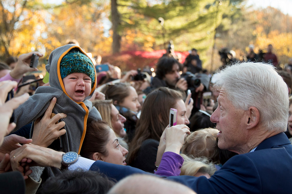 . A baby cries as former President Bill Clinton, right, greets supporters outside Douglas G. Grafflin School in Chappaqua, N.Y., Tuesday, Nov. 8, 2016, after he and his wife, Democratic presidential candidate Hillary Clinton voted. (AP Photo/Andrew Harnik)