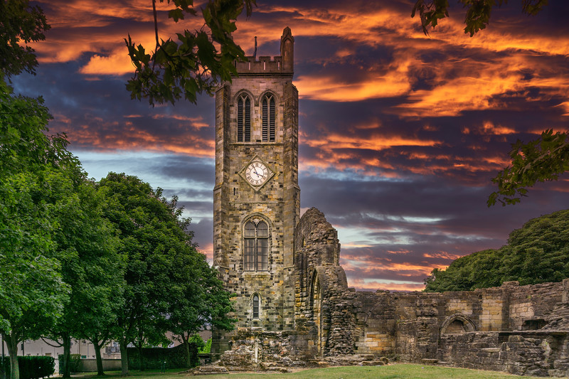 The Old Clock Tower Ruins at KIlwinning Abbey at the end of the day in front of a dramatic red Sky.