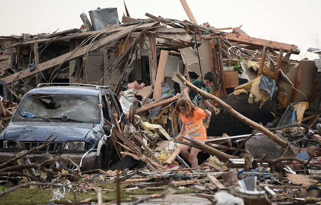 . Peterson Zatterlee and Abby Madi look for their dogs  among the destroyed buildings and overturned cars. 