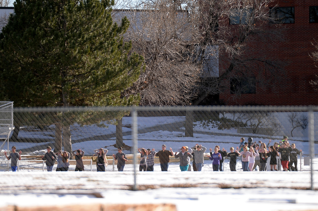 . CENTENNIAL, CO - Students with their arms up are escorted to the football field after being evacuated fro the school. At a about 12:30 pm a student was spotted inside Arapahoe High School carrying a shotgun December 13, 2013. The gunman was targeting a teacher at the school. The gunman shot two students in the process and then turned the gun on himself. DECEMBER 13:  (John Leyba, The Denver Post)