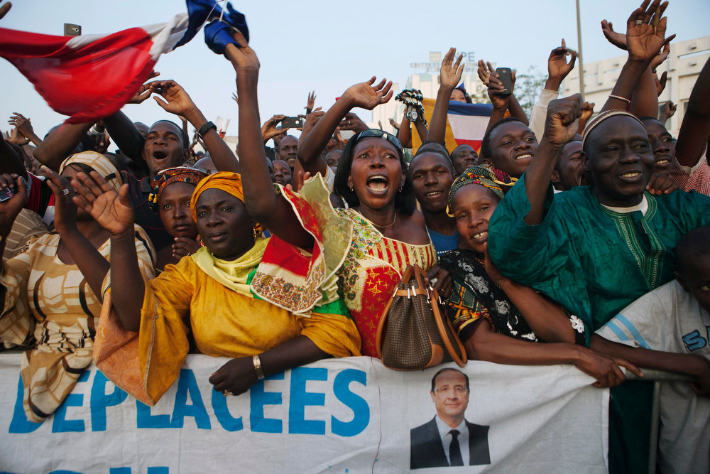 Description of . Malians cheer as France\'s President Francois Hollande (not pictured) speaks at Independence Plaza in Bamako, Mali February 2, 2013. France will withdraw its troops from Mali once the Sahel state has restored sovereignty over its national territory and a U.N.-backed African military force can take over from the French soldiers, Hollande said on Saturday. REUTERS/Joe Penney
