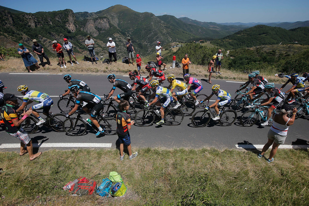 . Daryl Impey of South Africa, wearing the overall leader\'s yellow jersey, Christopher Froome of Britain, center with number 1, and Cadel Evans of Australia, center in red with number 31, climb Croix de Mounis pass with the pack during the seventh stage of the Tour de France cycling race over 205.5 kilometers (128.5 miles) with start in Montpellier and finish in Albi, southern France, Friday July 5, 2013. (AP Photo/Laurent Cipriani)