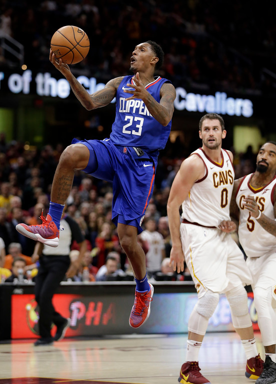 . Los Angeles Clippers\' Lou Williams (23) drives to the basket as Cleveland Cavaliers\' Kevin Love (0) and JR Smith (5) watch in overtime during an NBA basketball game, Friday, Nov. 17, 2017, in Cleveland. The Cavaliers won 118-113. (AP Photo/Tony Dejak)