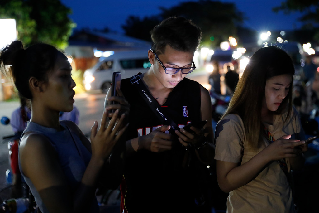 . People check their mobile phones for update while waiting at a military airbase during emergency helicopter evacuation in Chiang Rai province, northern Thailand, Monday, July 9, 2018. Four more of the boys trapped for over two weeks in a flooded cave in northern Thailand were brought out on Monday, an official said, bringing to eight the number extracted in a high-stakes rescue operation. (AP Photo/Vincent Thian)