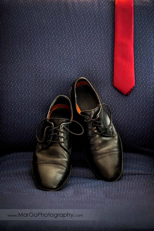 groom's wedding shoes and red tie on blue chair in San Diego Hyatt Regency Mission Bay Hotel
