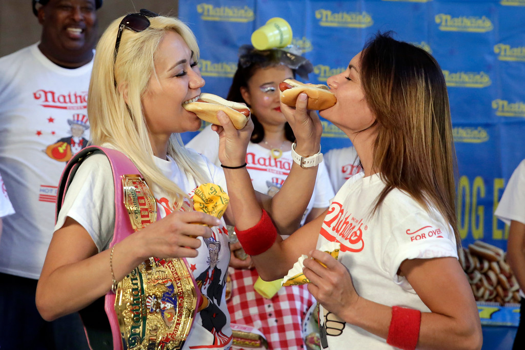 . Current women\'s champion Miki Sudo, left, of Las Vegas, and challenger Michelle Lesco, of Tuscon, Ariz., feed each other a hot dog Monday, July 3, 2017, during the weigh-in for the 2017 Nathan\'s Hot Dog Eating Contest, in Brooklyn Borough Hall, in New York. Ms. Suto weighed-in at 126 pounds, while Ms. Lesco tipped the scales at 104.5 pounds.(AP Photo/Richard Drew)