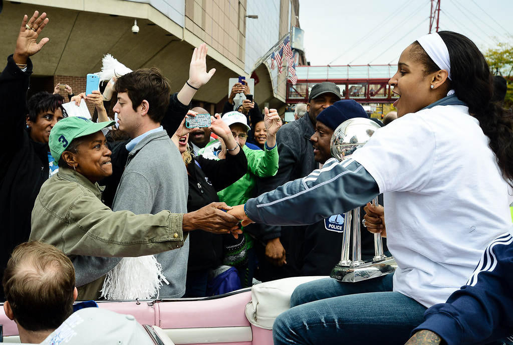 . Maya Moore, holding the WNBA championship trophy, reaches out to shake hands with a grateful fan. (Pioneer Press: Ben Garvin)