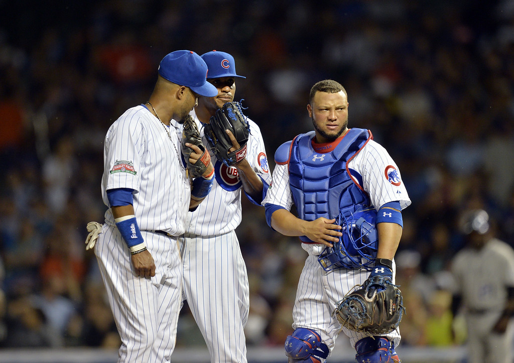 . Third baseman Emilio Bonifacio #64 (L) and catcher Welington Castillo #5 of the Chicago Cubs talk with starting pitcher Edwin Jackson #36 during the fourth inning against the Colorado Rockies on July 29, 2014 at Wrigley Field in Chicago, Illinois.  (Photo by Brian Kersey/Getty Images)