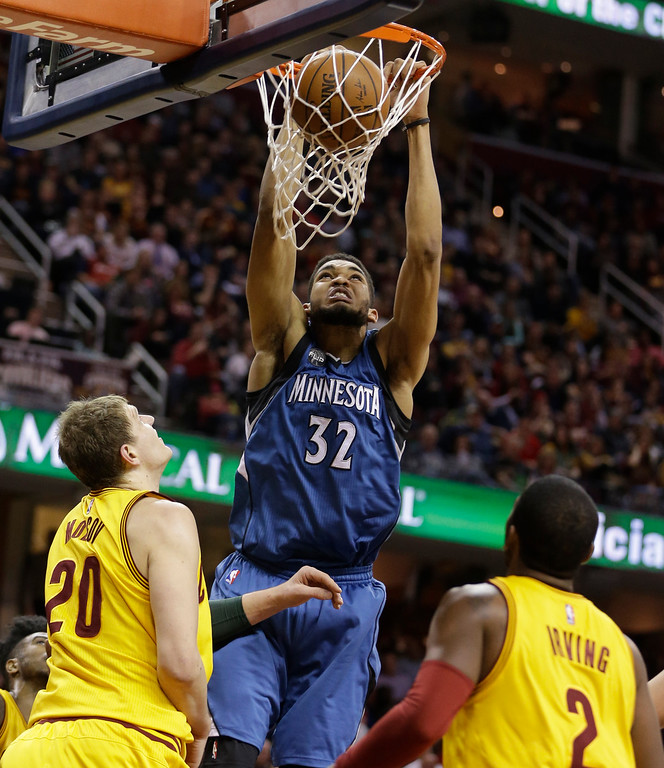 . Minnesota Timberwolves\' Karl-Anthony Towns (32) dunks the ball against Cleveland Cavaliers\' Timofey Mozgov (20), from Russia, and Kyrie Irving (2) in the second half of an NBA basketball game Monday, Jan. 25, 2016, in Cleveland. The Cavaliers won 114-107. (AP Photo/Tony Dejak)