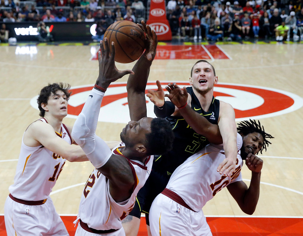 . Cleveland Cavaliers\' Cedi Osman (16), left, Jeff Green (32) and John Holland (10), right, battle Atlanta Hawks forward Mike Muscala (31) for a rebound during the second half of an NBA basketball game Friday, Feb. 9, 2018, in Atlanta. Cleveland won 123-107. (AP Photo/John Bazemore)