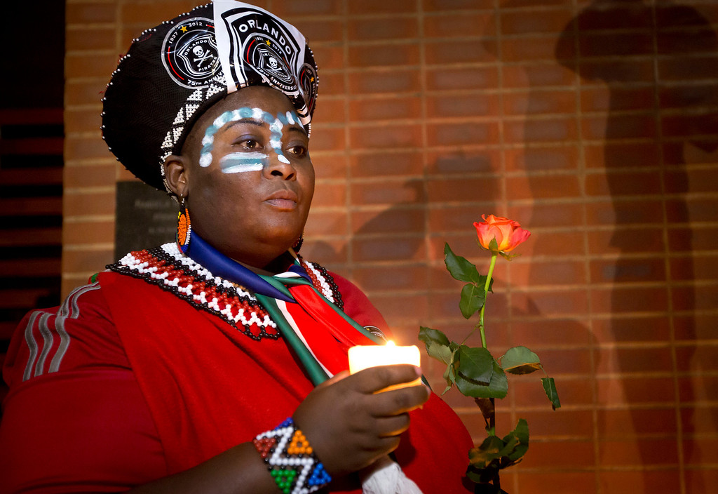 . Soweto resident Joy Chauke holds a candle as she arrives to lay flowers outside the old house of Nelson Mandela in Soweto, Johannesburg, South Africa Friday, Dec. 6, 2013. Flags were lowered to half-staff and people in black townships, in upscale mostly white suburbs and in South Africa\'s vast rural grasslands commemorated Nelson Mandela with song, tears and prayers on Friday while pledging to adhere to the values of unity and democracy that he embodied. (AP Photo/Ben Curtis)