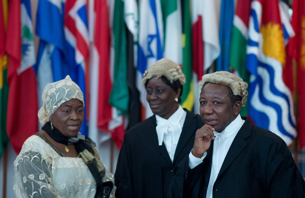 Description of . (FILES) - Picture taken on November 29, 2012 shows Ghana's representative Anthony Gyambiby (R) and other members of the delegation during a break of a hearing of the International Tribunal for the Law of the Sea of the case