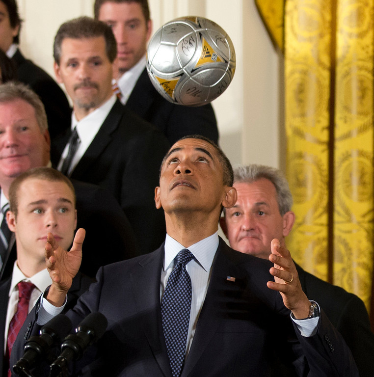 . Los Angeles Kings hockey coach Darryl Sutter, right, and others, watch as President Barack Obama bounces the soccer ball off his forehead during a ceremony  in the East Room of the White House in Washington, Tuesday, March 26, 2013, honoring the Stanley Cup champion Los Angeles Kings and the Major League Soccer champion LA Galaxy for their 2012 championship seasons.   (AP Photo/Manuel Balce Ceneta)