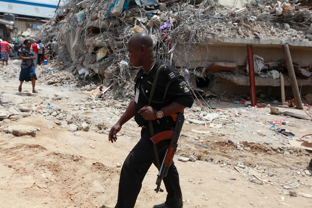 . A police officer walks amongst the rubble of a collapsed building belonging to the Synagogue Church of All Nations, as rescue workers search for survivors, in Lagos, Nigeria, Saturday, Sept. 13, 2014. The building was being extended, adding 2 additional floors when it collapsed. (AP Photo/Sunday Alamba)
