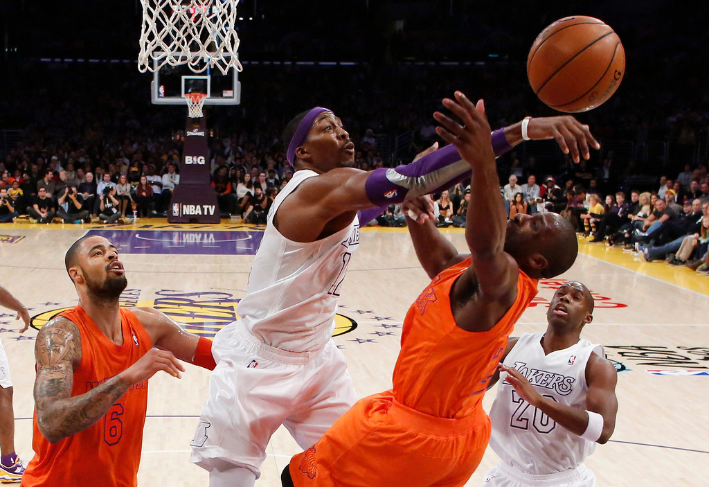 . Los Angeles Lakers\' Dwight Howard (2nd R) blocks a shot by New York Knicks\' Raymond Felton as Knicks\' Tyson Chandler (L) and Lakers\' Jodie Meeks (R) look on during the second half of their NBA basketball game in Los Angeles December 25, 2012. REUTERS/Danny Moloshok