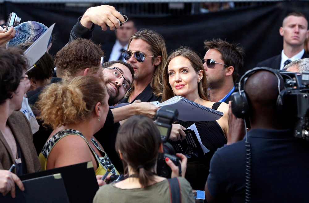 ". U.S. Actress Angelina Jolie takes a picture with a fan upon arrival with her partner U.S. actor Brad Pitt for the world premiere of his film ""World War Z\"" in London June 2, 2013.  REUTERS/Neil Hall"