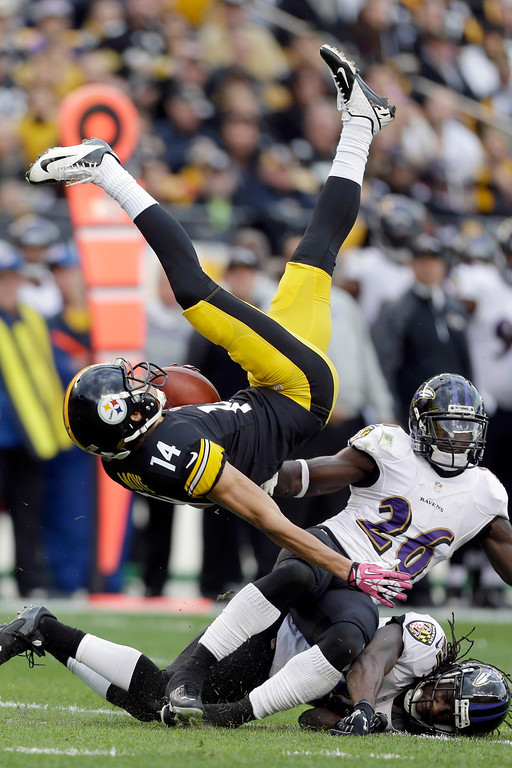. Pittsburgh Steelers wide receiver Derek Moye (14) flips over after making a catch over Baltimore Ravens free safety Matt Elam (26) and cornerback Lardarius Webb in the second quarter of an NFL football game in Pittsburgh on Sunday, Oct 20, 2013. (AP Photo/Gene J. Puskar)