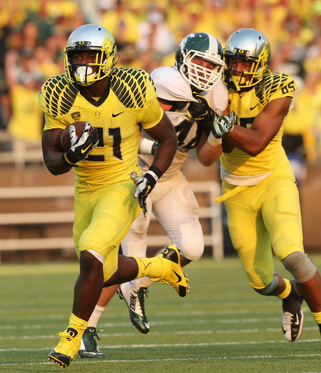 . Oregon\'s Royce Freeman, left, slides by Michigan State\'s Marcus Rush as he is blocked by Oregon\'s Pharaoh Brown on his way to a 4th quarter touch down against the Spartans in their college football game in Eugene, Oregon,. Saturday Sept. 6, 2014. (AP Photo/Chris Pietsch)