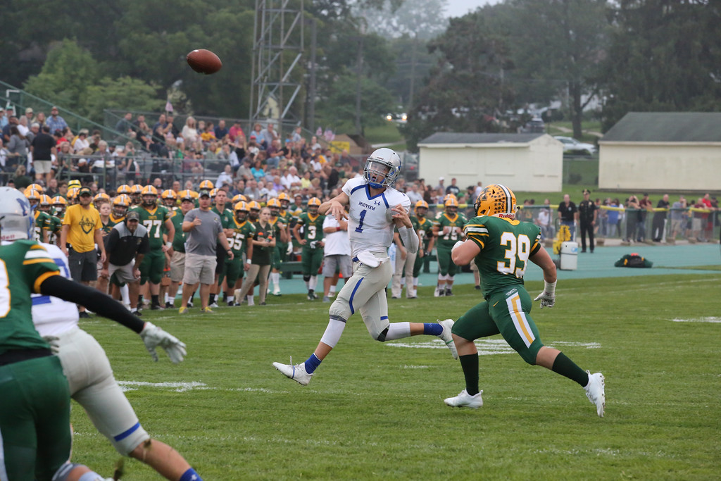 . David Schneider - The Morning Journal<br> Midview quarterback Andrew Gooch throws a touchdown to Edwin Ralat as Amherst\'s Connor Emch closes in on Sept. 14.