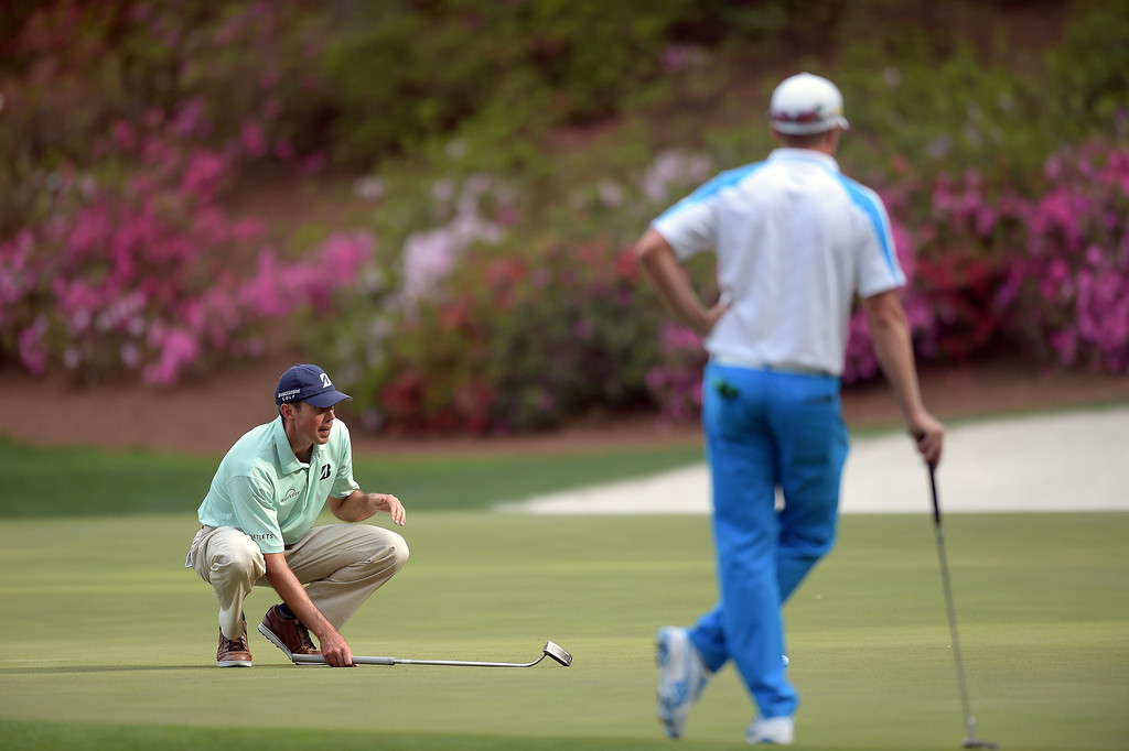 . Matt Kuchar (L) of the US lines up a putt shot on the 13th green as Jonas Blixt (R) of Sweden watches during the final round of the 78th Masters Golf Tournament at Augusta National Golf Club on April 13, 2014 in Augusta, Georgia.    JIM WATSON/AFP/Getty Images