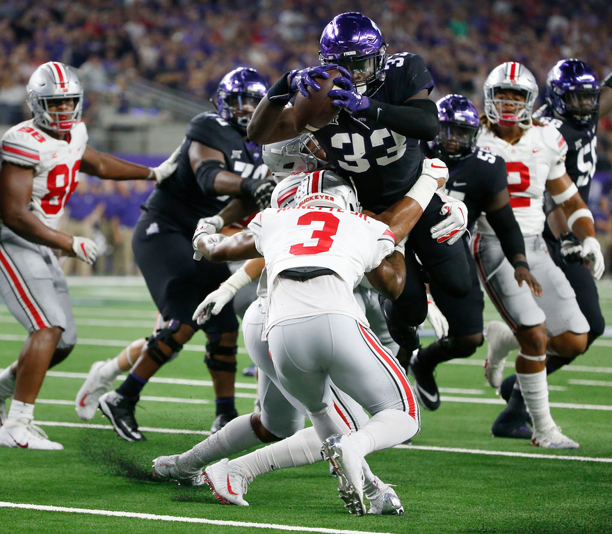 . TCU running back Sewo Olonilua (33) scores a touchdown as Ohio State\'s Damon Arnette Jr. attempts to take him down during the first half of an NCAA college football game in Arlington, Texas, Saturday, Sept. 15, 2018. (AP Photo/Michael Ainsworth)