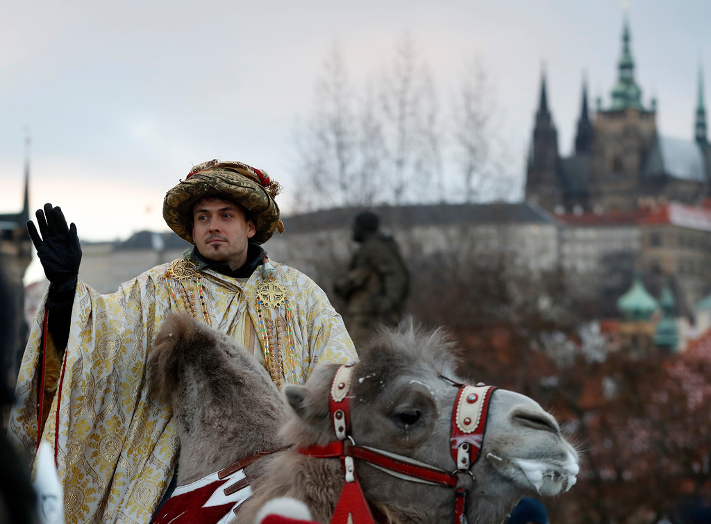 . A man dressed as one of the Three Kings rides on a camel during a procession of the Three Kings across the Charles Bridge in Prague, Czech Republic, Friday, Jan. 6, 2017. The procession, which annually marks the end of the Christmas festivities in Prague, is a re-enactment of the journey of the Three Kings to visit the infant Jesus. Prague Castle is in the background. (AP Photo/Petr David Josek)