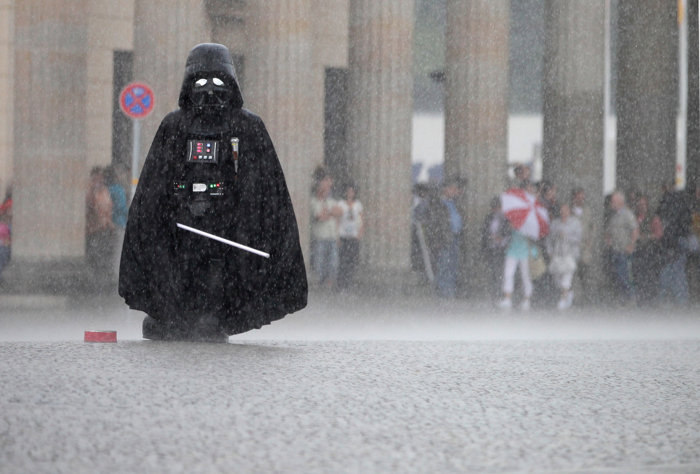 Description of . A Darth Vader actor waits for tourists who want to be photographed together with him, in front of the Brandenburg Gate during a thunderstorm in Berlin, Germany, Tuesday, June 14, 2011. (AP Photo/Michael Sohn)