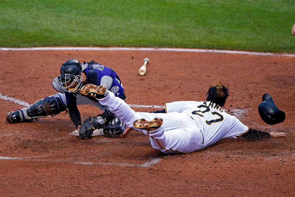 . Colorado Rockies catcher Tony Wolters, left, makes the tag on Pittsburgh Pirates\' Jung Ho Kang (27) for the out during the fourth inning of a baseball game in Pittsburgh, Saturday, May 21, 2016. Kang was attempting to score from third on a fielder\'s choice by Pirates\' Matt Joyce. (AP Photo/Gene J. Puskar)