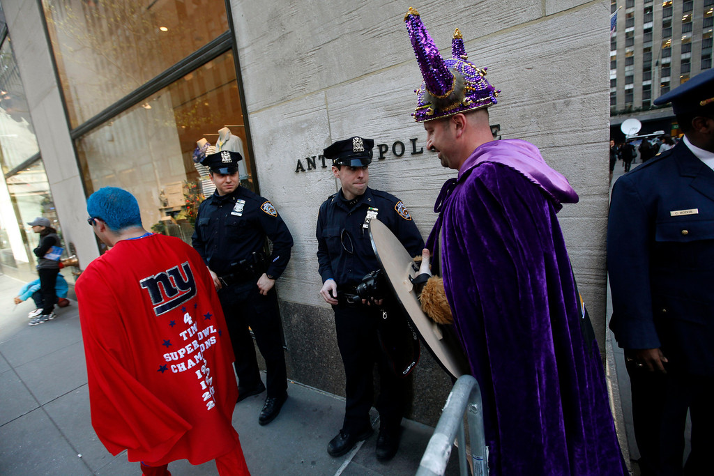 . Fans walk past police officers as they make their way into Radio City Music Hall before the first round of the NFL football draft, Thursday, April 25, 2013, in New York. (AP Photo/Jason DeCrow)