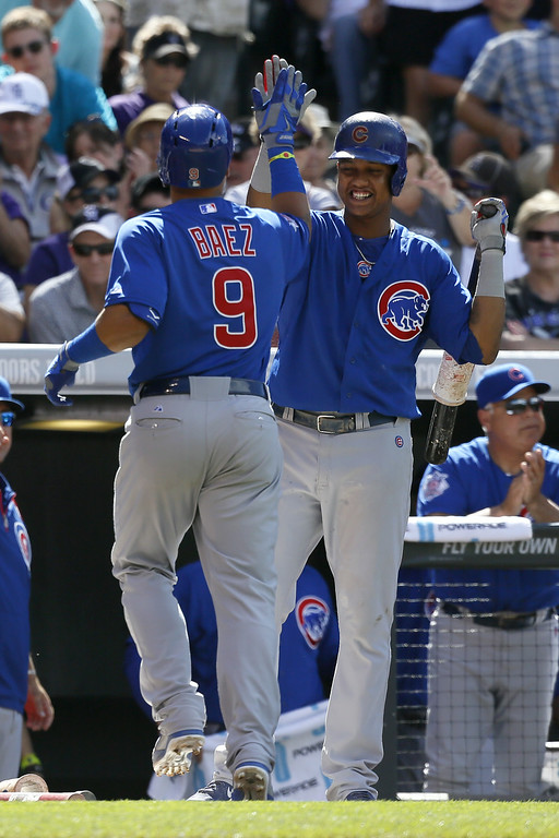 . Chicago Cubs second baseman Javier Baez #9 gets a high five from teammate Starlin Castro #13 after hitting a two-run home run against the Colorado Rockies at Coors Field on August 7, 2014 in Denver, Colorado.  The Chicago Cubs defeated the Colorado Rockies 6-2.  (Photo by Trevor Brown, Jr./Getty Images)