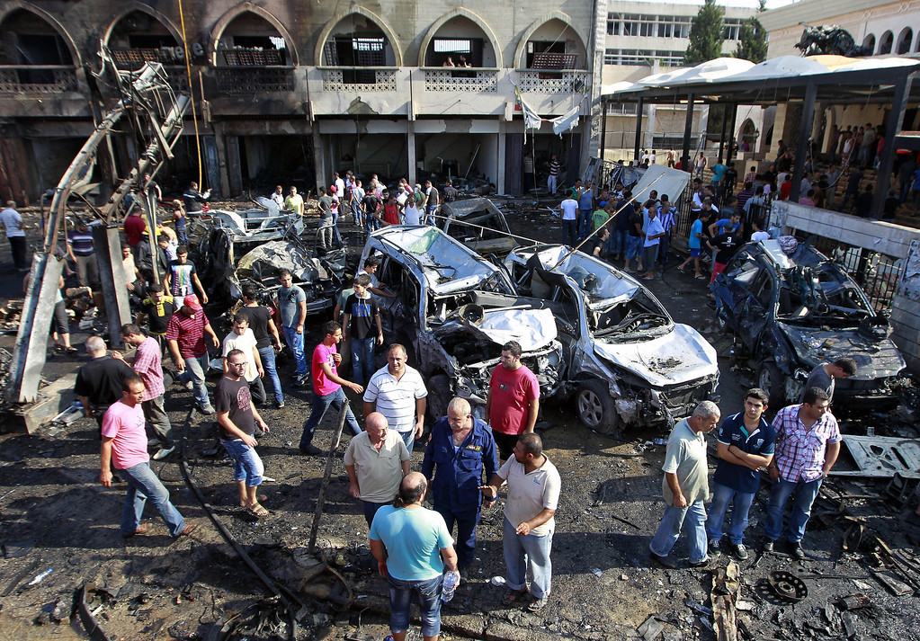 . People gather outside the Al-Taqwa mosque the amid charred cars and wide damage, in the northern city of Tripoli, Lebanon, Friday Aug. 23, 2013.  (AP Photo/Bilal Hussein)