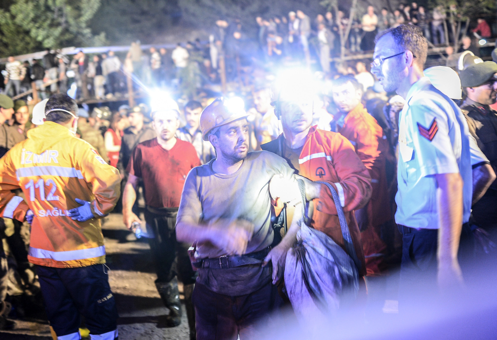 ". A miner came out helped by friends after an explosion in Manisa on May 13, 2014. Four miner were killed and as many as 300 trapped after a mine collapse in the western Turkish city of Manisa, a local official said. ""At least 200-300 workers were working in the mine when an electric fault caused an explosion,\"" the mayor of Soma, a district of Manisa, told private NTV television. (BULENT KILIC/AFP/Getty Images)"