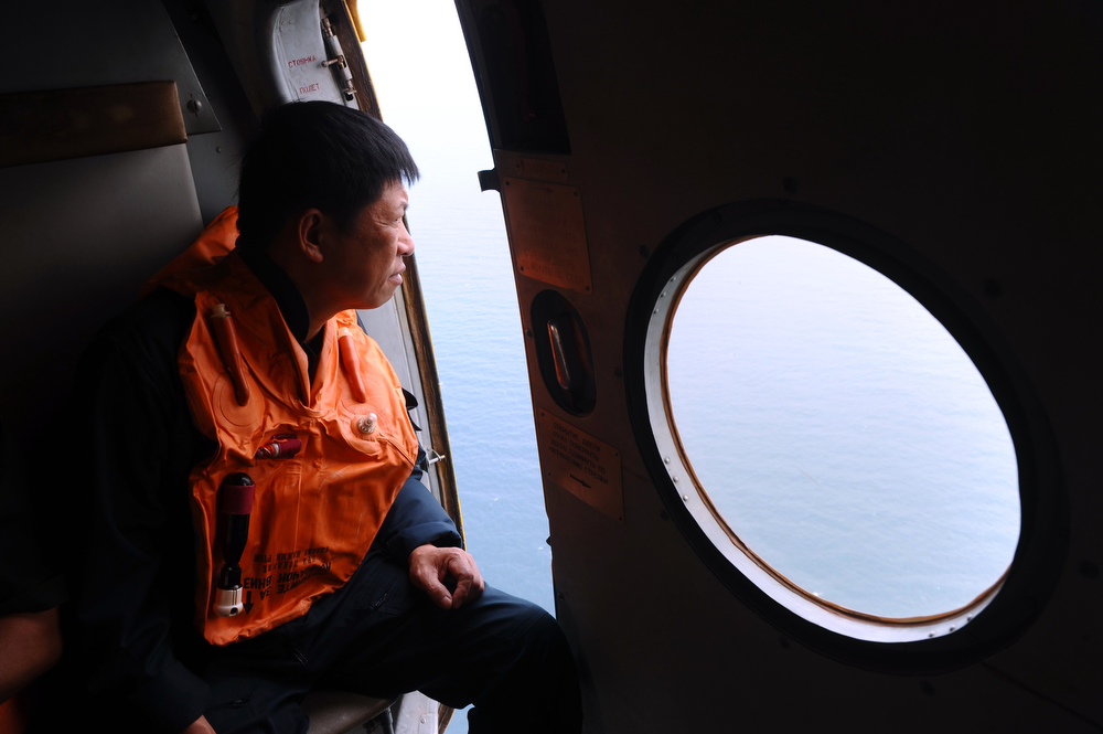 . This picture taken aboard a Vietnamese Air Force Russian-made MI-171 helicopter shows a crew member looking out from a door during a search flight some 200 km over the southern Vietnamese waters off Vietnam\'s island Phu Quoc on March 11, 2014 as part of continued efforts aimed at finding traces of the missing Malaysia Airlines MH370. Malaysian police said on March 11 one of two suspect passengers who boarded a missing passenger jet was an Iranian illegal immigrant, as relatives of some of the 239 people on board said they were losing hope for a miracle. (HOANG DINH NAM/AFP/Getty Images)