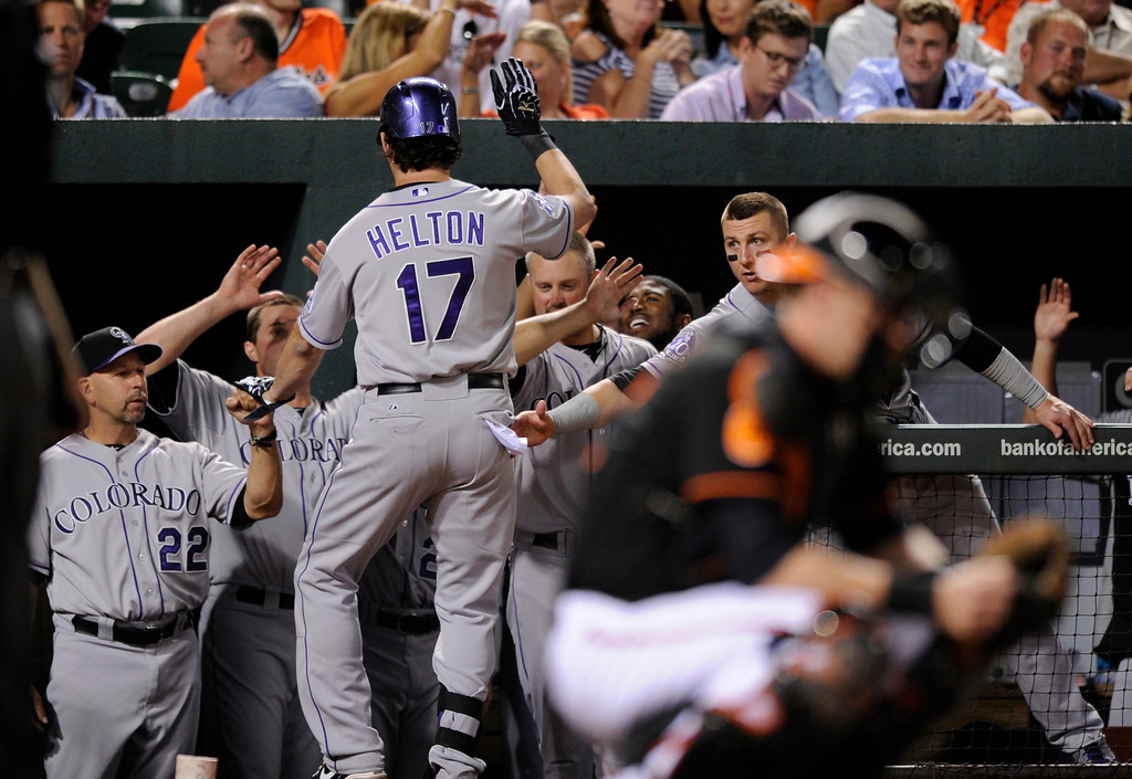 . Colorado Rockies\' Todd Helton (17) celebrates his home run with manager Walt Weiss (22) and others in the dugout against the Baltimore Orioles during the ninth inning of a baseball game, Friday, Aug. 16, 2013, in Baltimore. The Rockies won 6-3. (AP Photo/Nick Wass)